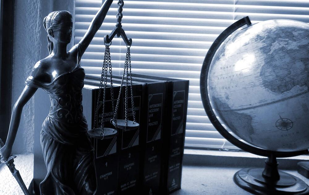 Photographie d'une statuette représentant la justice à côté de livres et d'un globe