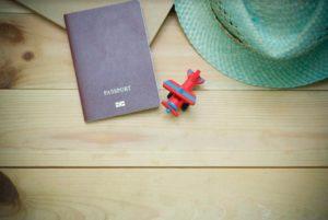 Photo d'un passeport, d'un jouet et d'un chapeau sur une table