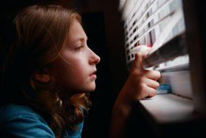 Photo d'une enfant qui regarde par la fenêtre